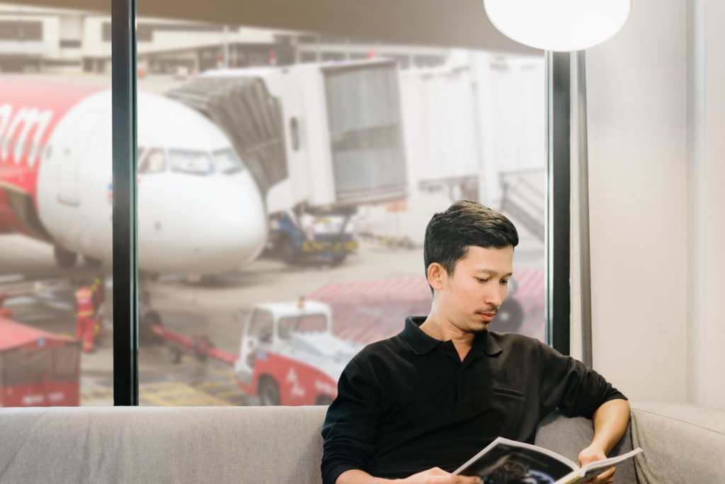 Asian man reading a magazine in the lounge at the airport in selective focus.